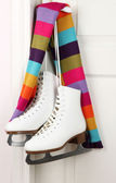 Figure skates hanging on a door knob with scarf — Stock Photo