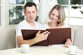 Beautiful young romantic couple with photo, at home — Stock Photo