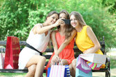 Three beautiful young woman taking picture in summer park — Stock fotografie