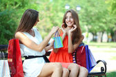 Two beautiful young woman with shopping bags in park — Stock fotografie