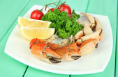 Boiled crab claws on white plate with salad leaves and tomatoes,on wooden table background — Stock Photo