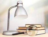 Lámpara de mesa y libros sobre el escritorio en la habitación — Foto de Stock