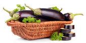 Verse aubergines in rieten mand geïsoleerd op wit — Stockfoto