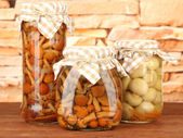 Delicious marinated mushrooms in glass jars, on wooden table on bright background — Stock Photo