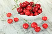 Körsbär bär i skål på träbord närbild — Stockfoto