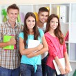 Group of happy beautiful young students at room — Stock Photo