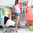Beautiful girl thinking what to dress in walk-in closet — Stock Photo #30360843
