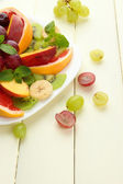 Assortment of sliced fruits on plate, on white wooden table — Foto de Stock