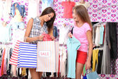 Two beautiful young woman in shop with shopping bags — Foto de Stock