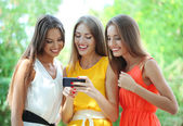Three beautiful young woman with smartphone in summer park — Stock Photo