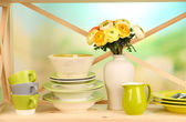 Beautiful dishes on wooden cabinet on natural background — Stock Photo