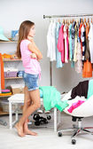 Beautiful girl thinking what to dress in walk-in closet — Стоковое фото
