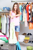 Beautiful girl throws out unnecessary clothes in room — Stock Photo