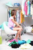 Beautiful girl chooses clothes in room — Stock Photo