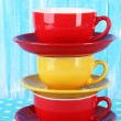 Three cups on blue background — Stock Photo