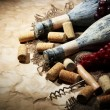 Stock Photo: Old bottles of wine, grapes and corks on old paper background