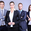 Business team standing in row on grey background — Stock Photo