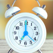 Alarm clock on table on bright background — Stock Photo