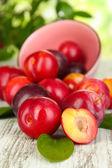 Prunes mûres sur une table en bois sur fond naturel — Photo