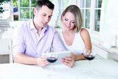 Foto de jovem casal tomada com tablet no restaurante — Fotografia Stock