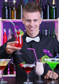 Portrait of handsome barman with different cocktails cocktail, at bar — Foto de Stock
