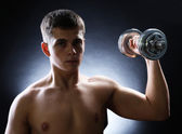 Handsome young muscular sportsman execute exercise with dumbbell on dark background — Stock Photo