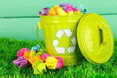 Recycling bin on green grass on color wooden background — ストック写真