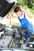 Young auto mechanic repairing car engine outdoors — Stock Photo