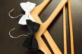 Black and white bow ties on wooden hangers, on wooden background — Stock Photo