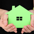 Paper house in hand on green background — Stock Photo