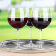 Wine glasses on  tray, on bright background — Stock Photo