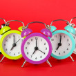 Colorful alarm clock on red background — Stockfoto