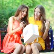 Two beautiful young woman with shopping bags in park — Stock Photo