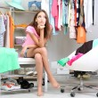 Beautiful girl thinking what to dress in walk-in closet — Stock Photo #30413823