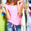 Beautiful girl with lots clothes in room background — Stock Photo #30413835