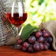 Ripe delicious grapes with glass of wine on table on bright background — Stock Photo