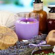 Still life with lavender candle, soap, massage balls, bottles, soap and fresh lavender, on wooden table on bright background — Stock Photo
