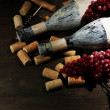 Stock Photo: Old bottles of wine, grapes and corks on wooden background