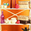 Beautiful white shelves with different home related objects, on color wall background — Lizenzfreies Foto