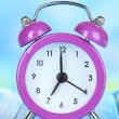 Alarm clock on table on blue background — Stok fotoğraf