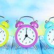 Colorful alarm clocks on table on blue background — Stock Photo #30417227