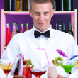 Portrait of handsome barman with different cocktails cocktail, at bar — Photo