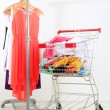 Shopping cart with clothing, on gray wall background — Stock Photo #30417483