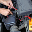 Auto mechanic uses multimeter voltmeter to check voltage level in car battery — Stock Photo