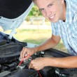 Young driver uses multimeter voltmeter to check voltage level in car battery — Stock Photo #30417893