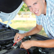 Young driver uses multimeter voltmeter to check voltage level in car battery — Stock Photo