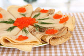 Delicious pancakes with red caviar on table in room — Stock Photo