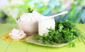 Fresh dairy products with greens on wooden table on natural background — Stock Photo