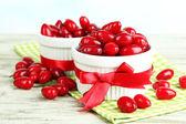 在木桌上的白杯新鲜山茱萸浆果 — 图库照片