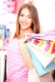 Beautiful young woman in shop with shopping bags — Stock Photo